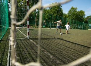 Sportive man playing football with little boy