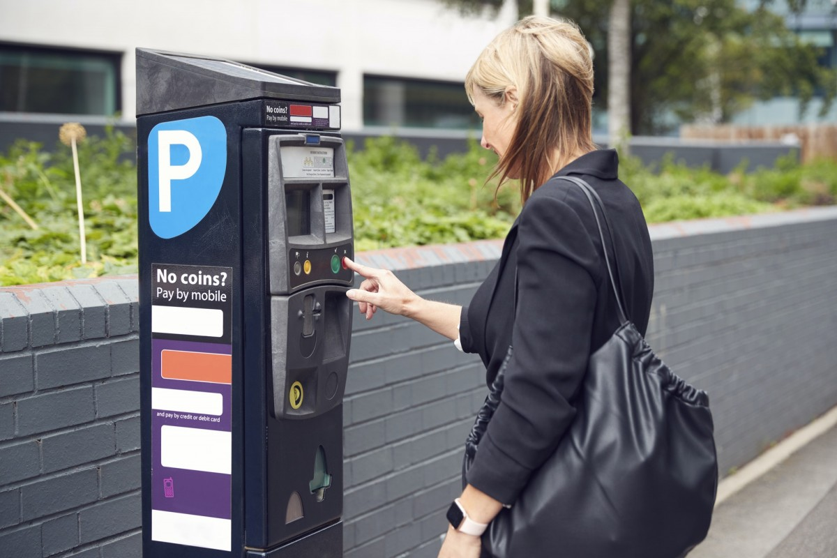 Mature Businesswoman Paying For Car Parking At Machine On City Street