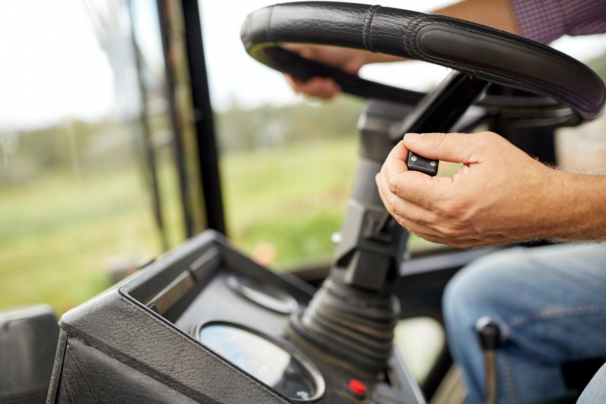 senior man driving tractor at farm
